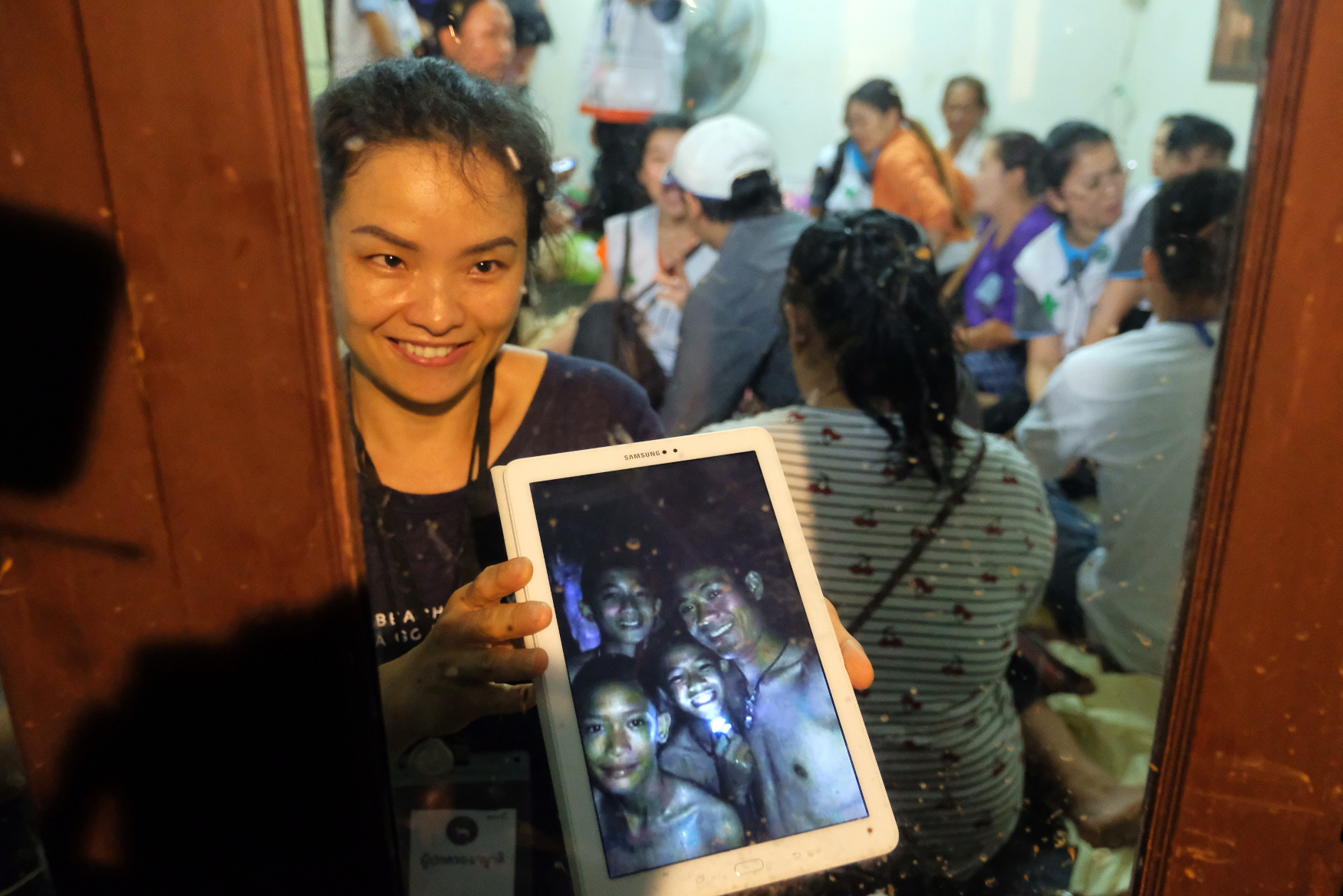 Relatives of the missing boys show photos of them after the 12 boys and their soccer coach have been found alive in the cave where they've been missing for over a week after monsoon rains blocked the main entrance on July 02, 2018 in Chiang Rai, Thailand. (Getty Images)