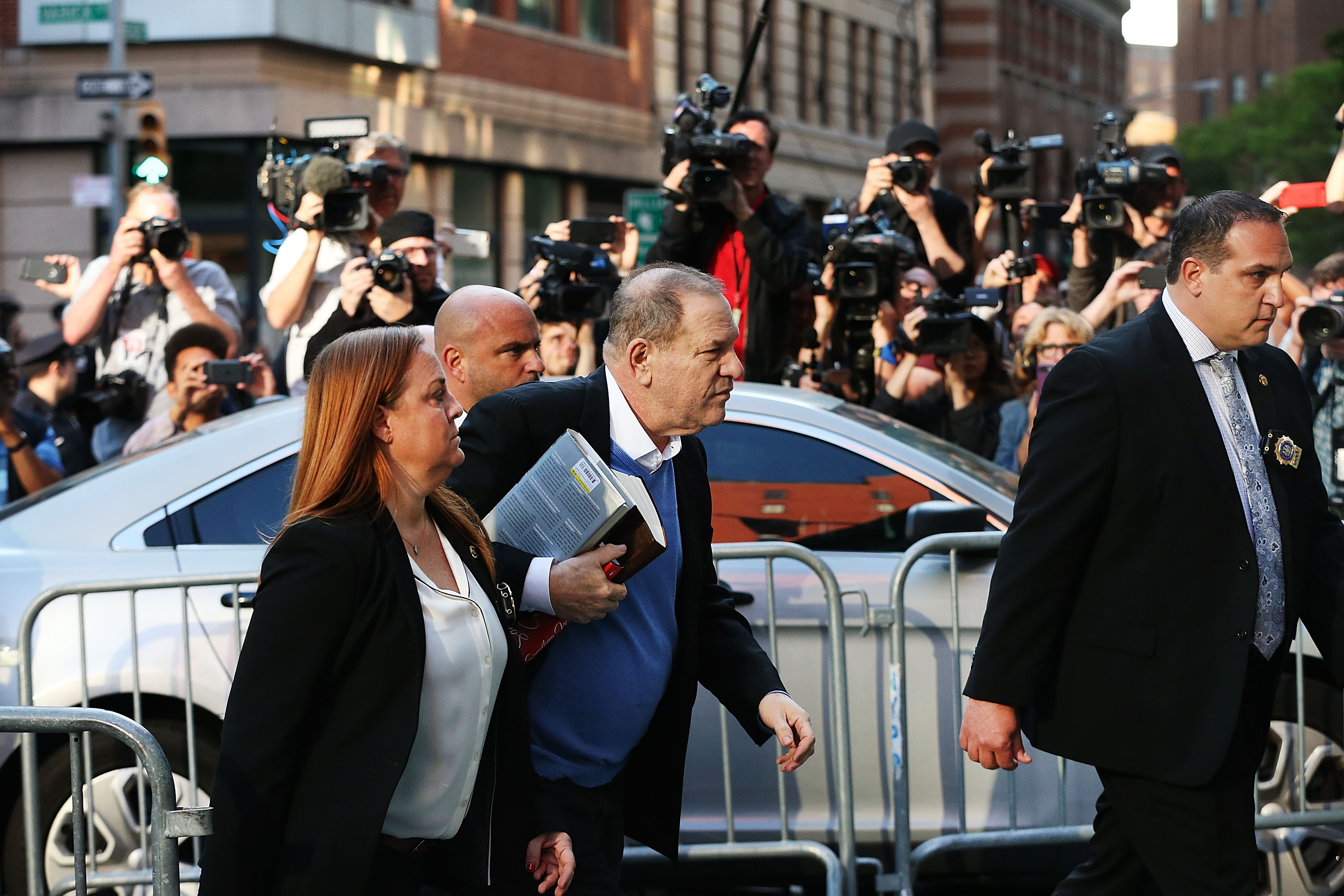 Harvey Weinstein arrives at the New York Police Department's First Precinct to turn himself in after being served with criminal charges by the Manhattan District Attorney's office on May 25, 2018 in New York City. The former movie producer faces charges in connection with accusations made by aspiring actress Lucia Evans who has said that Weinstein forced her to perform oral sex on him in his Manhattan office in 2004. Weinstein (66) has been accused by dozens of other women of forcing them into sexual acts using both pressure and threats. The revelations of his behavior helped to spawn the global #MeToo movement. Weinstein is carrying a biography of Elia Kazan.